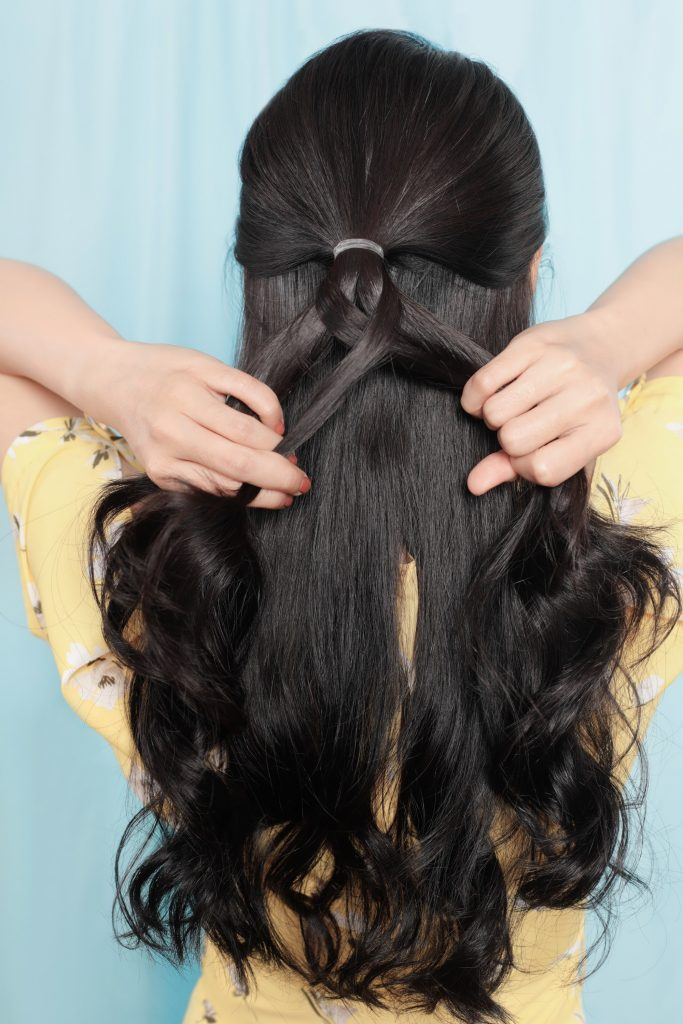 half up flower fishtail braid: Girl is showing how she makes the fishtail braid