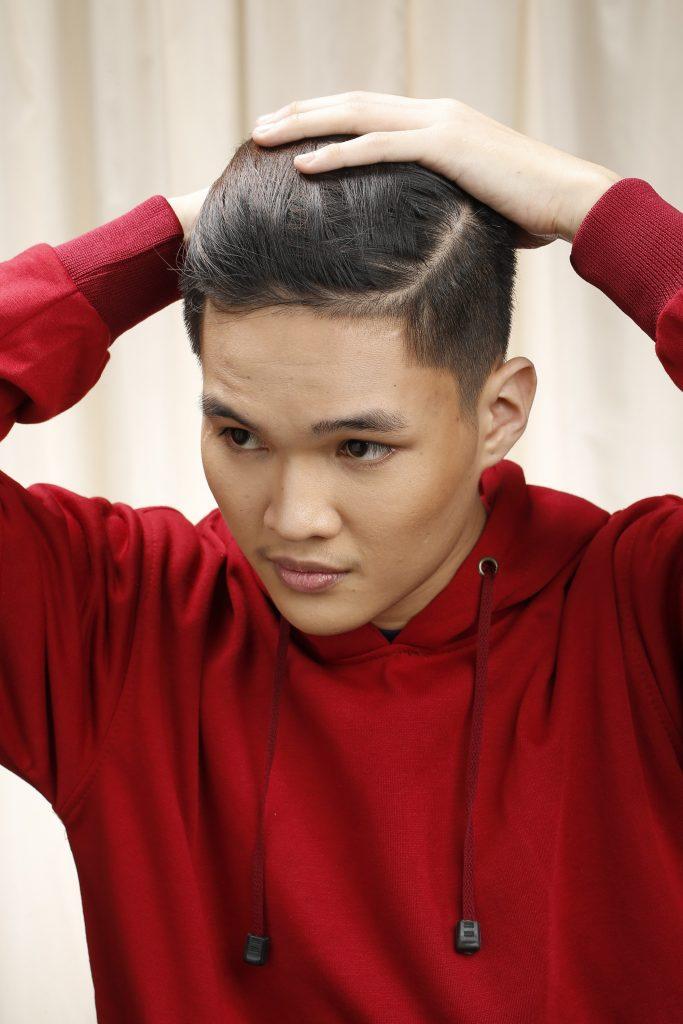 Model is seen gathering his hair to make the man bun braid