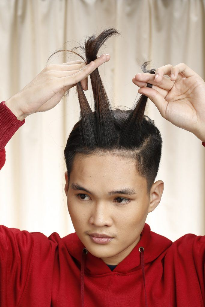 Model is seen sectioning his hair to make the man bun braid