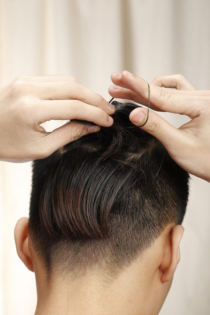 guy is tying an elastic to his hair