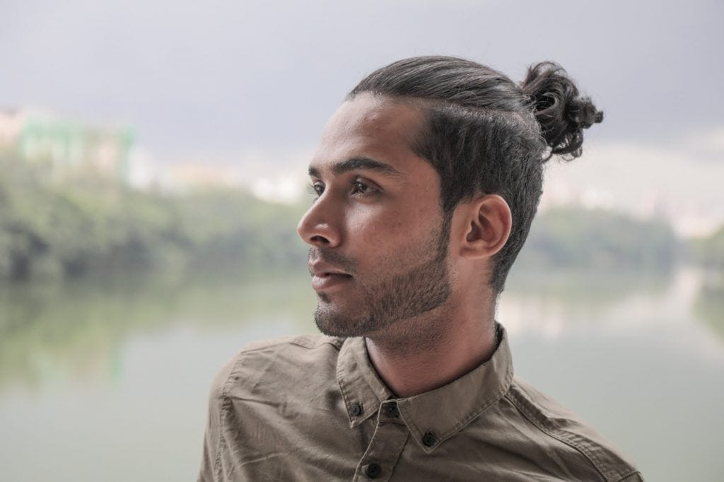 Man is facing sideways and his man bun haircut is made obvious