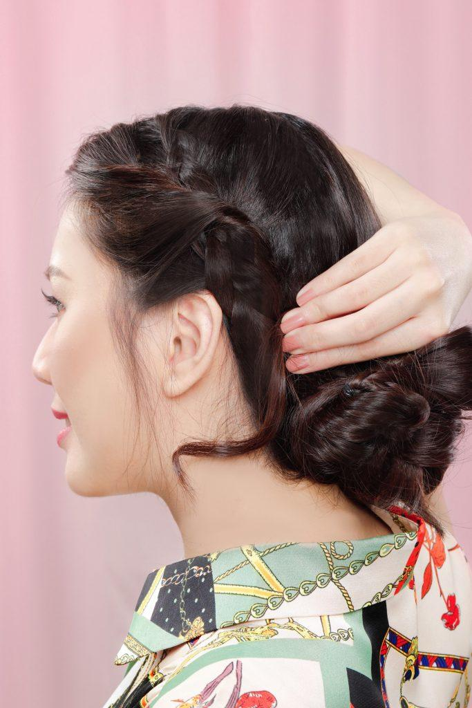 girl is holding her bangs behind her ear to connect it to her messy bun with headband braid