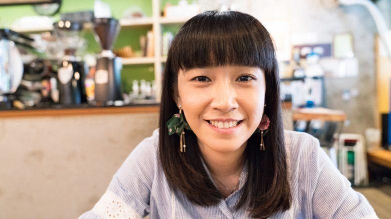 Asian woman with full bangs and shoulder-length hair smiling