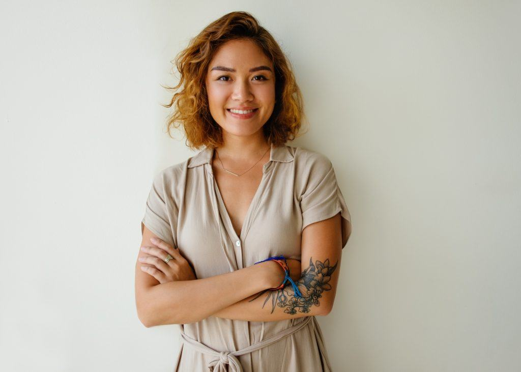 Asian woman with curly hair and honey hair color wearing a gray shirt