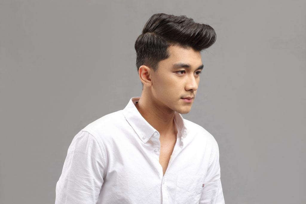 Asian man with barber's cut and pompadour hairstyle wearing a white polo