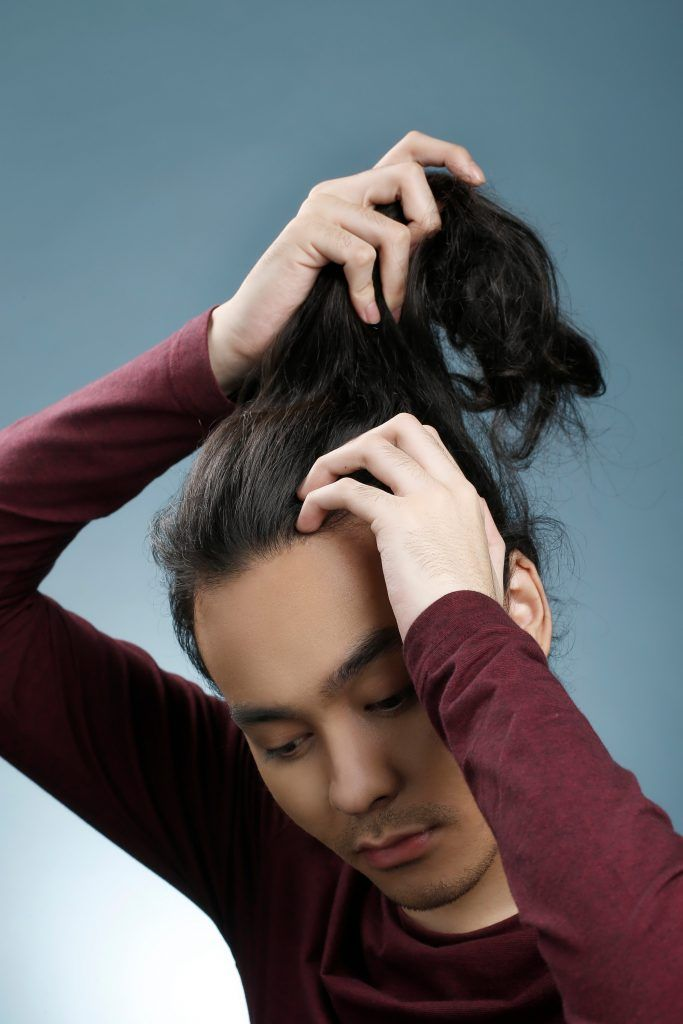 Model is gathering his hair to make a bun