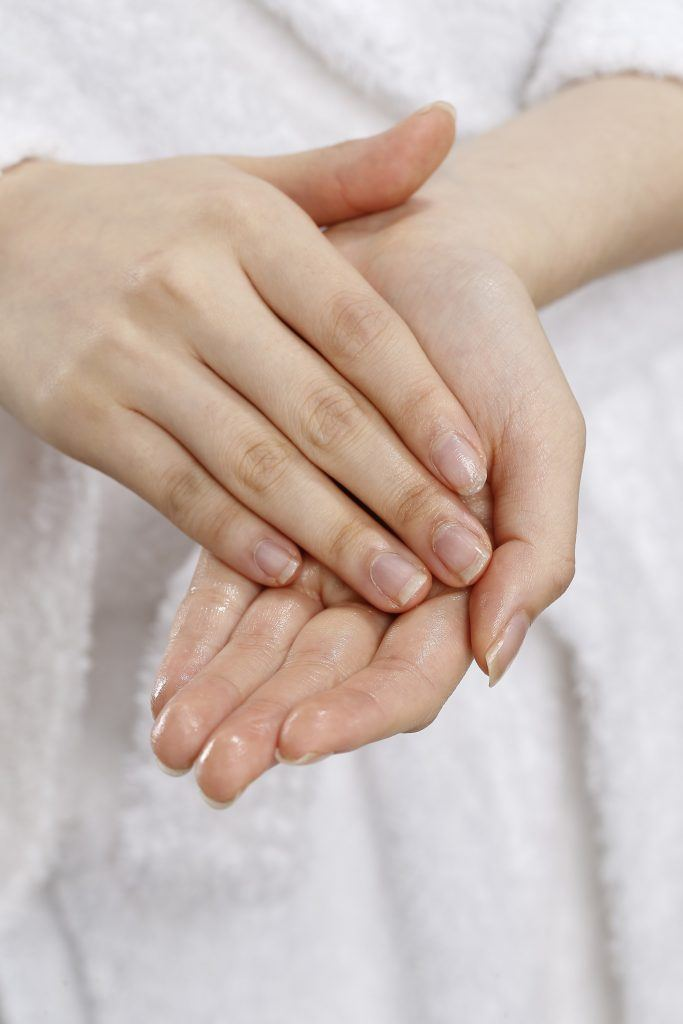 model's hands are seen with coconut oil