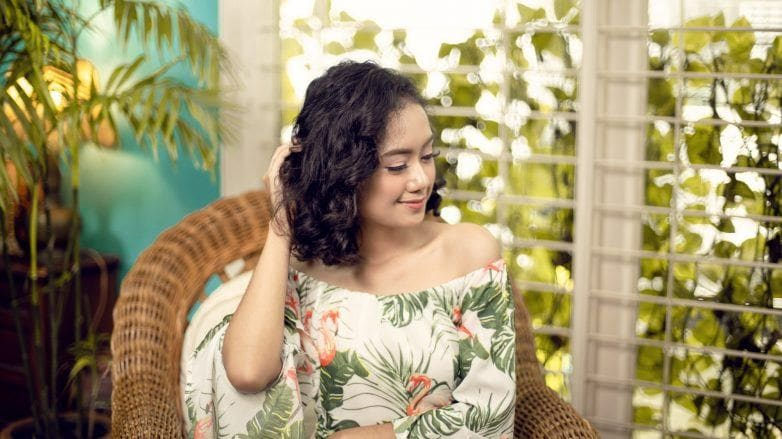 Conditioner for curly hair: Asian woman sitting on a chair and touching her curly hair
