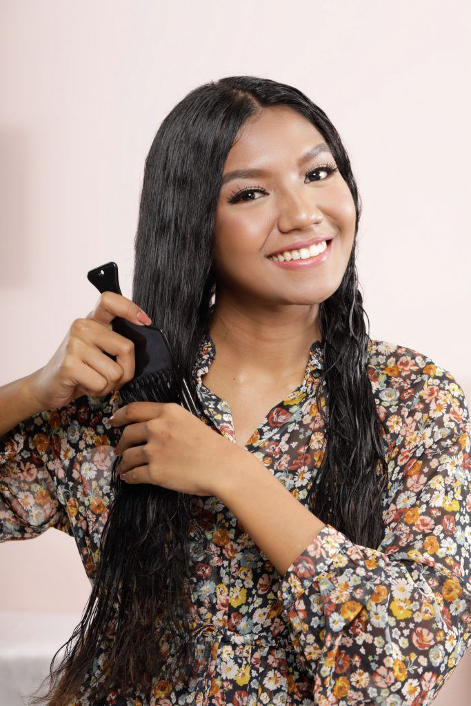 how to straighten hair without heat: girl is combing her hair with a wide-toothed comb