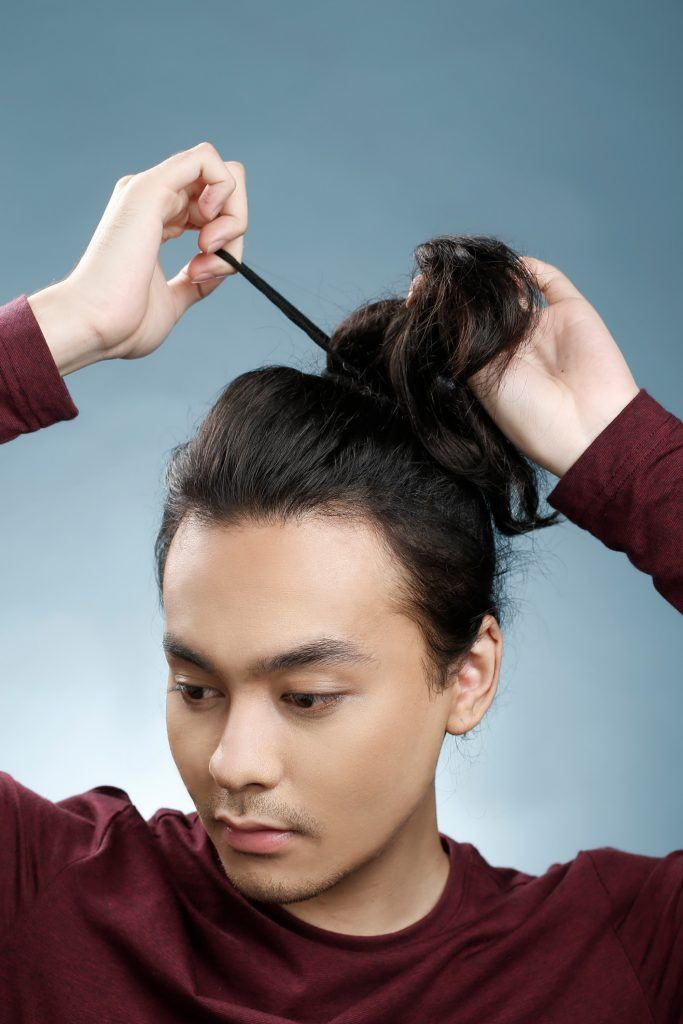 guy is tying his hair with an elastic