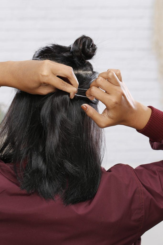girl is tying two small sections of hair below the first one