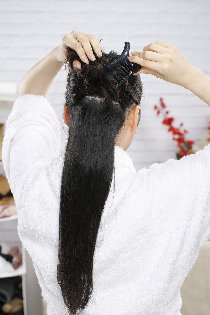 Girl's back view is seen as she releases another set of hair