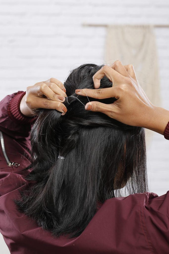 Girl is showing how she ties her ponytail
