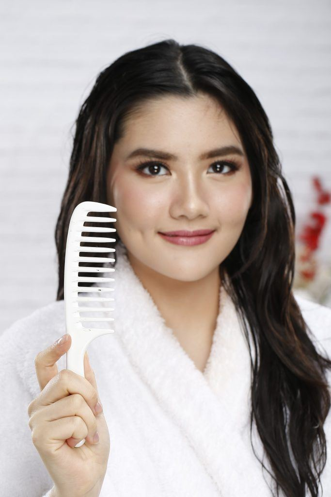 coconut oil for hair: girl is raising her wide-toothed comb to be used for untangling her hair