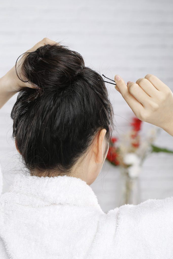 coconut oil for hair: Girl's back view is seen as she puts her hair up in a bun and secures it with bobby pins