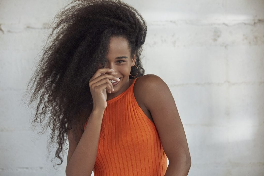 #MyHairMySay: Model has long and curly hair and is smiling giddily at the camera