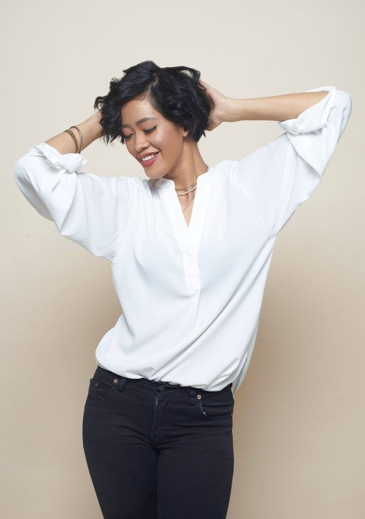 Haircuts for curly hair: Asian woman with curly short hair wearing a white blouse and black pants