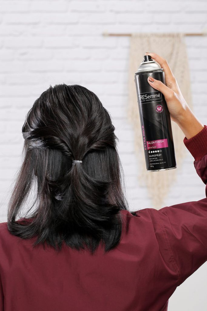 Asian woman spraying hairspray on her hair