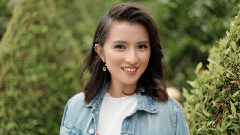 Asian woman with side bangs wearing a denim jacket