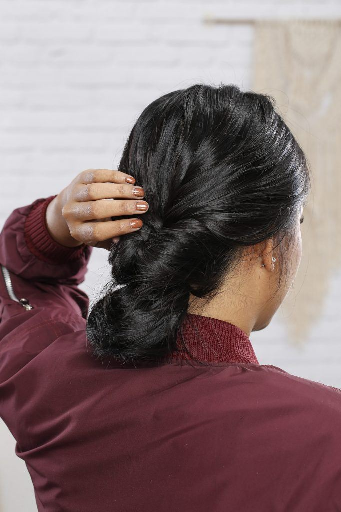 Girl's hand is trying to hide the tied section of her hair