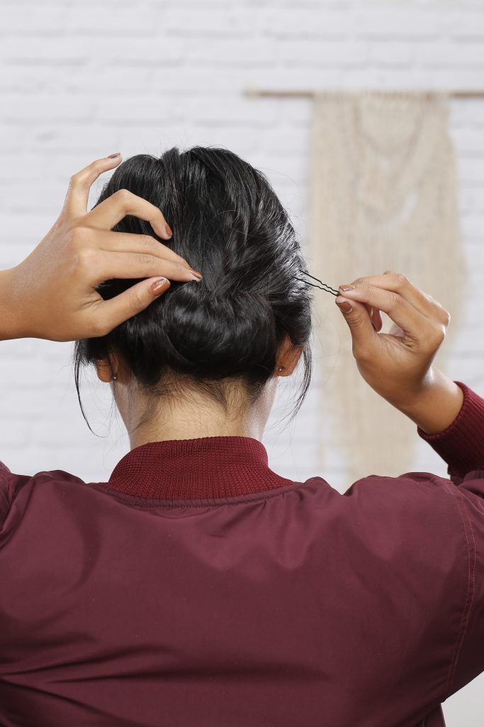 Girl is using bobby pins to secure the hair