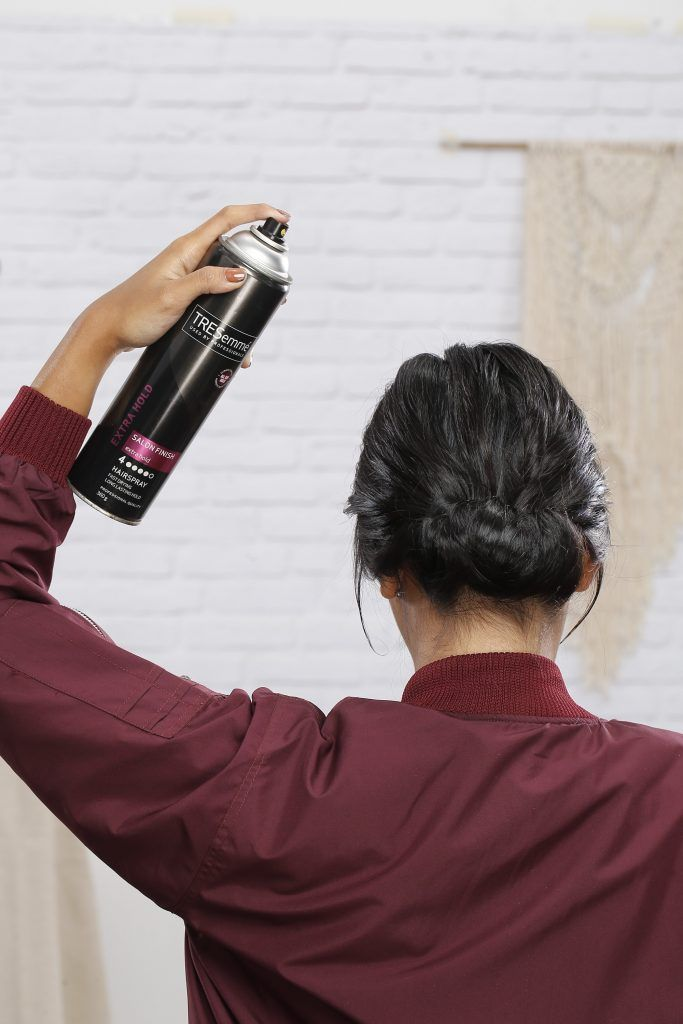 how to style short hair: girl is spraying hairspray on her hair