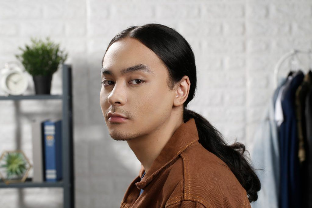 how to style men's long hair: guy wearing a brown jacket is looking at the camera with his low man ponytail