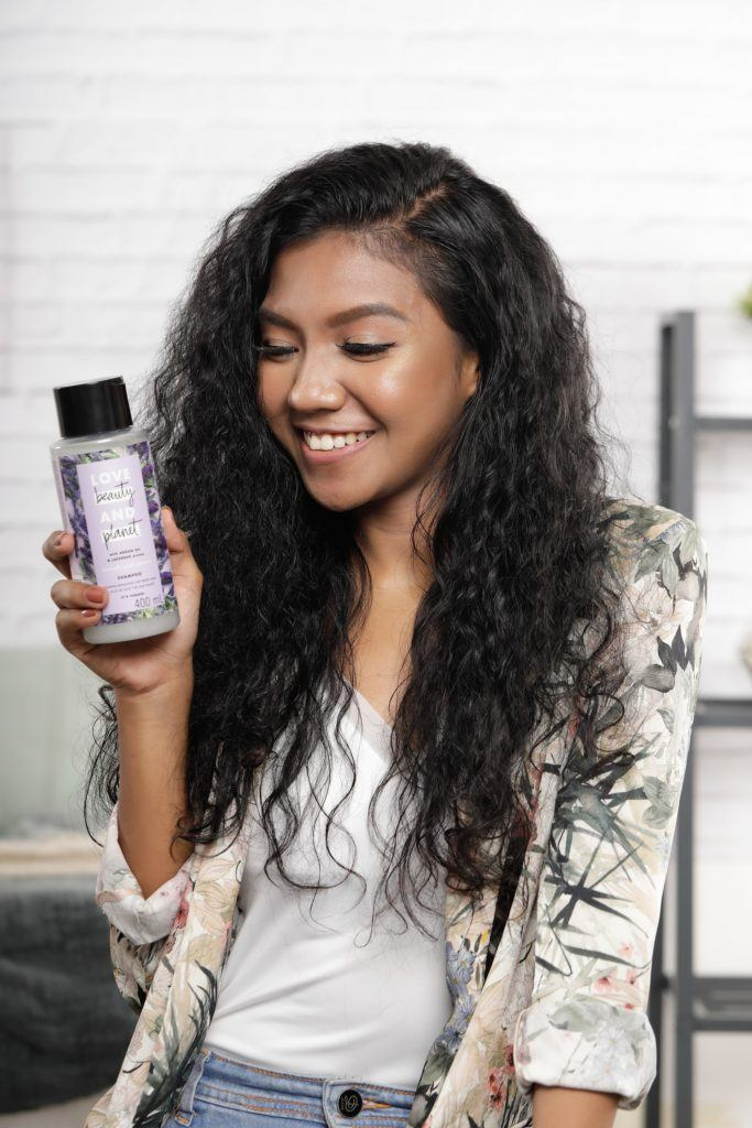 how to style curly hair: Girl is holding a bottle of shampoo
