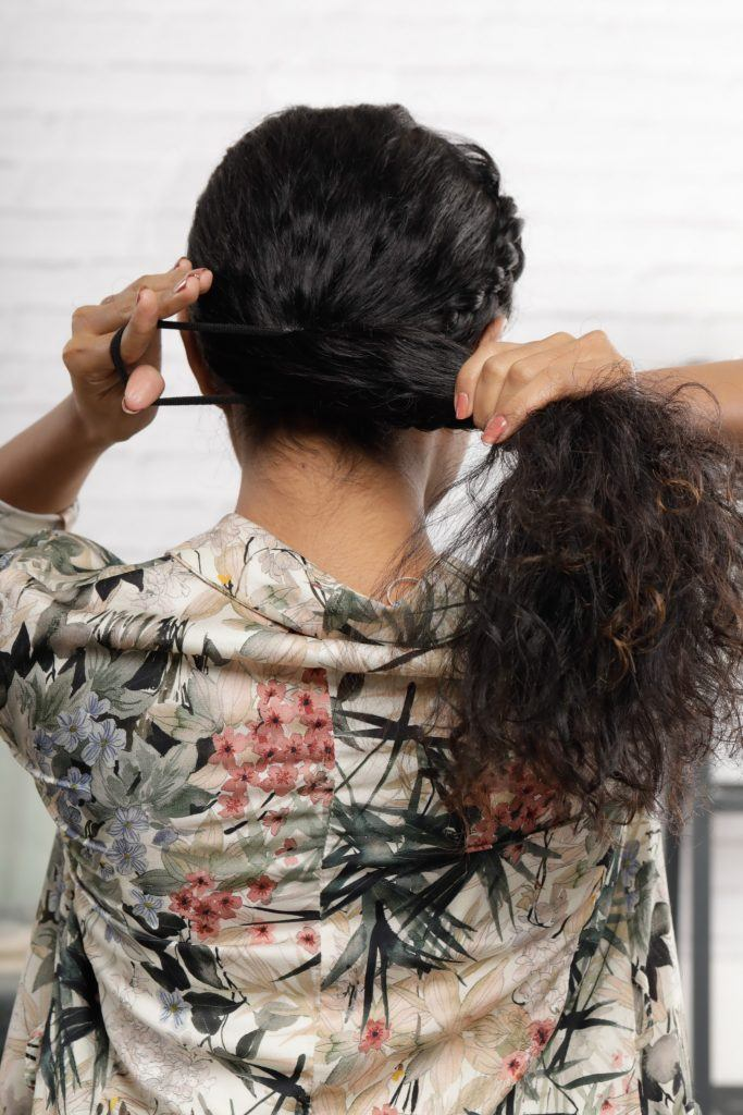 Girl's back view is seen where she is tying her hair into a ponytail