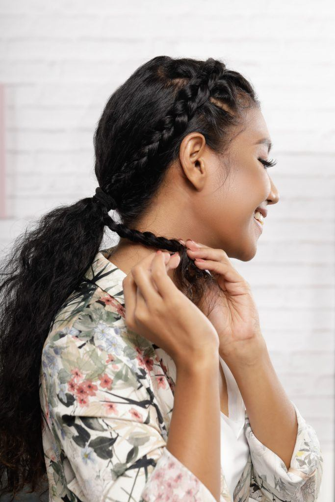 Girl's side view is shown and she is trying to remove the bobby pins from her braid