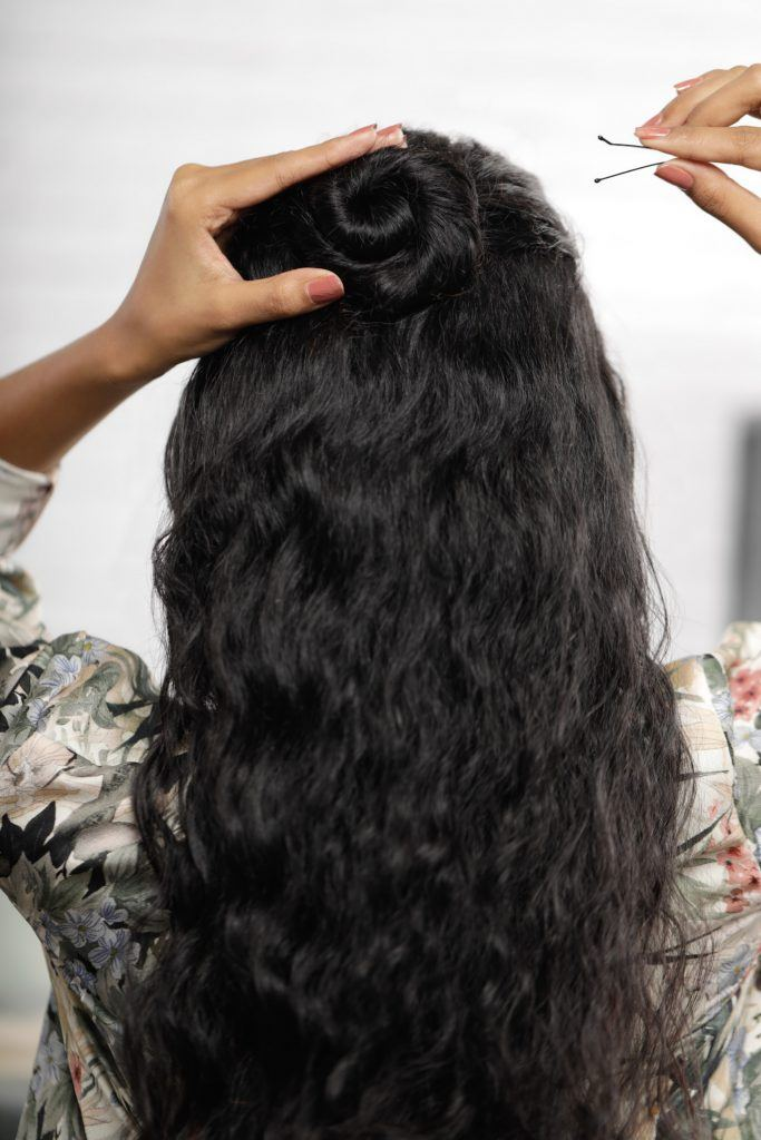 how to style curly hair: girl's back is turned as she shows how she secures her bun