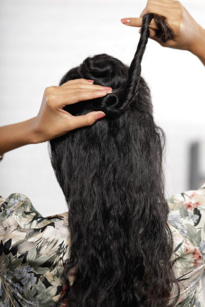 girl's back view is seen as she is turning her hair to make her second bun