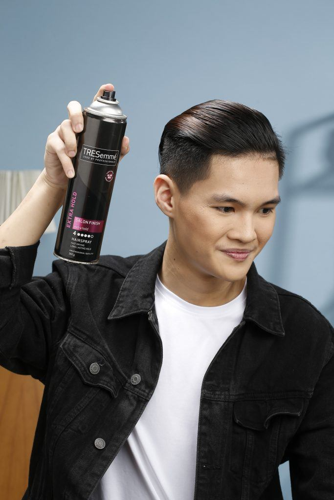 Model is spraying on hairspray on his slicked-back hair for men