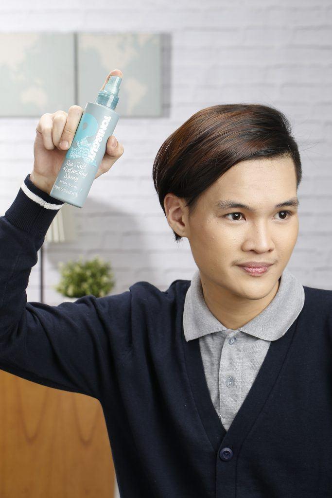 Asian man raising a bottle of texturising spray