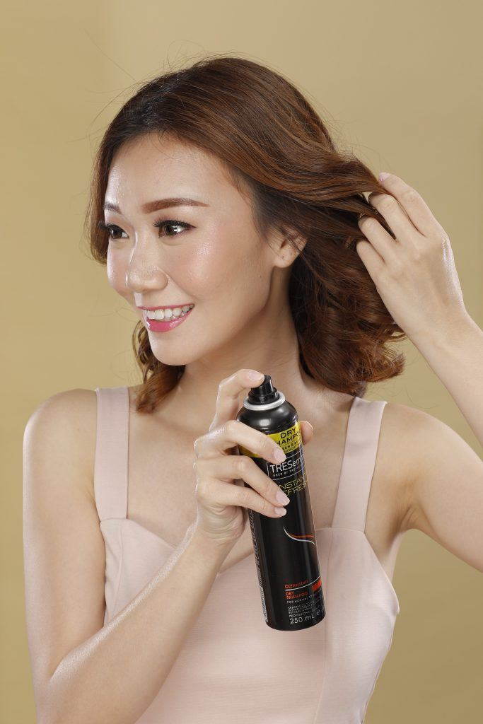 short hair updo with tendril: Girl is spraying dry shampoo on her hair