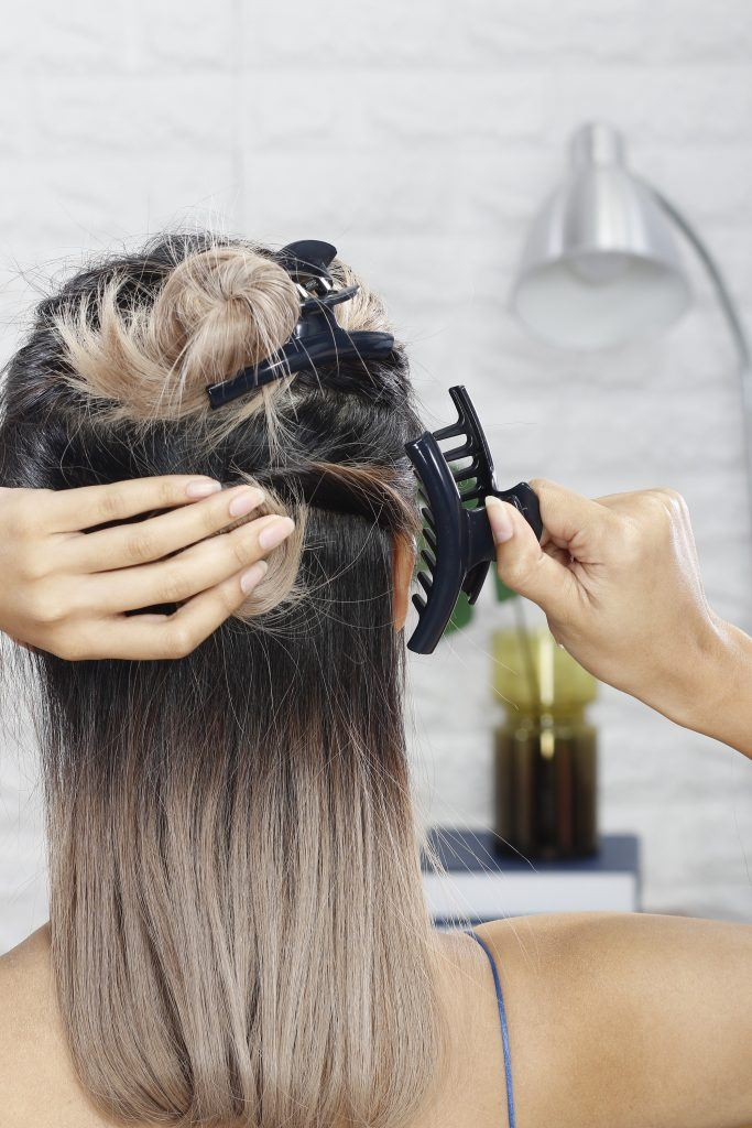 how to style a curly updo with headband: girl is making another bun and clamping it in place