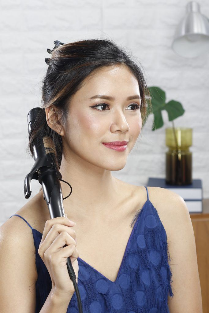how to style a curly updo with headband: girl is using a curling wand to curl her loose hair