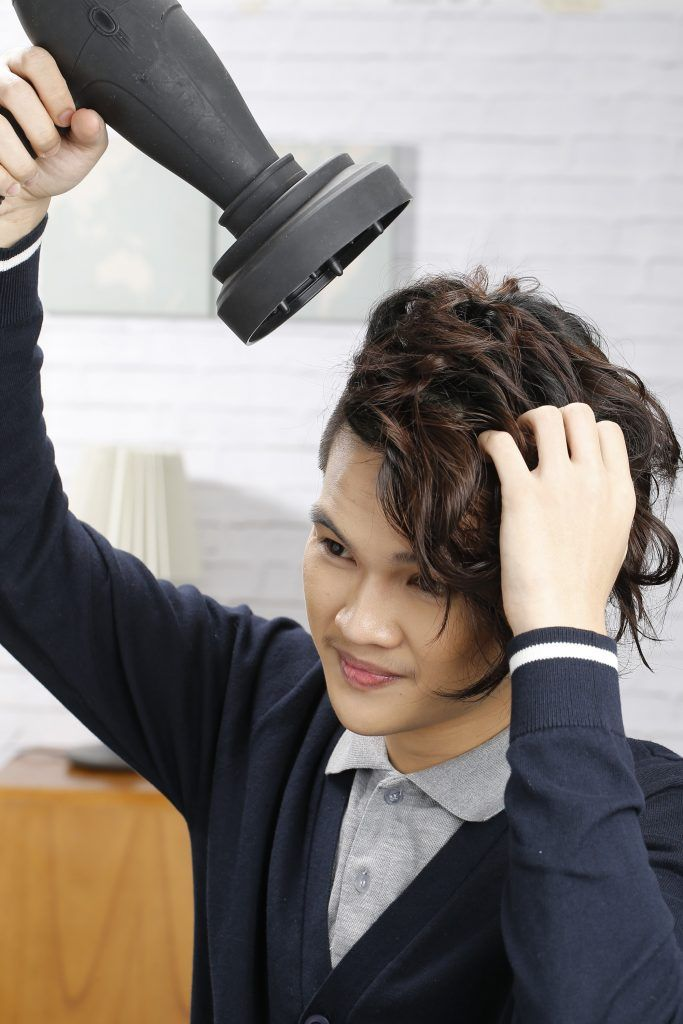messy hair tutorial for men: model is using a diffuser to maintain his hair's texture