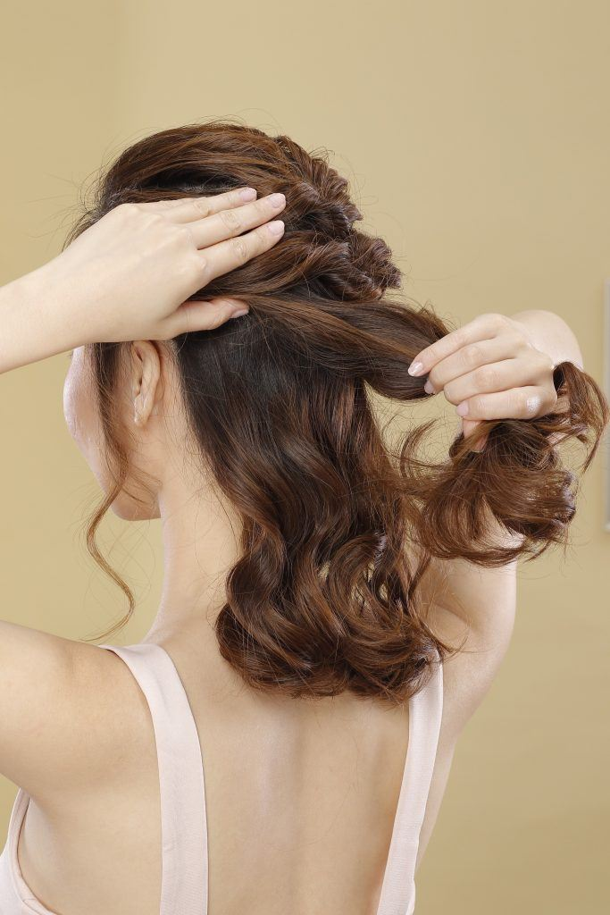 short hair updo with tendrils: model's hands are shown holding her hair