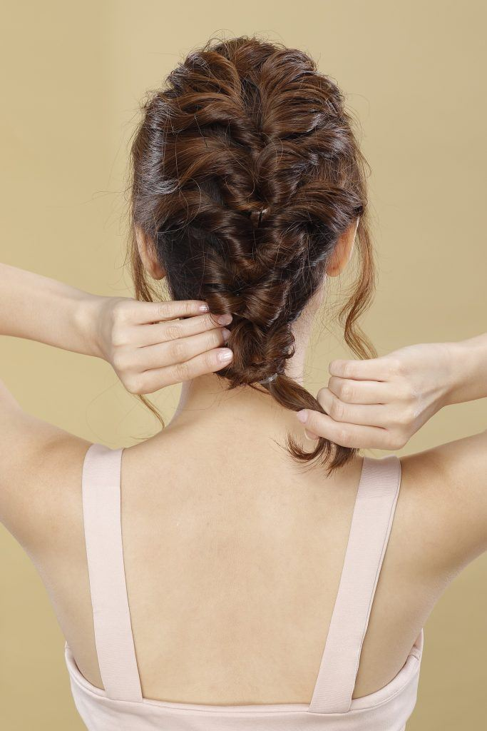 short hair updo with tendrils: girl is showing how she inserts her hair into the gap