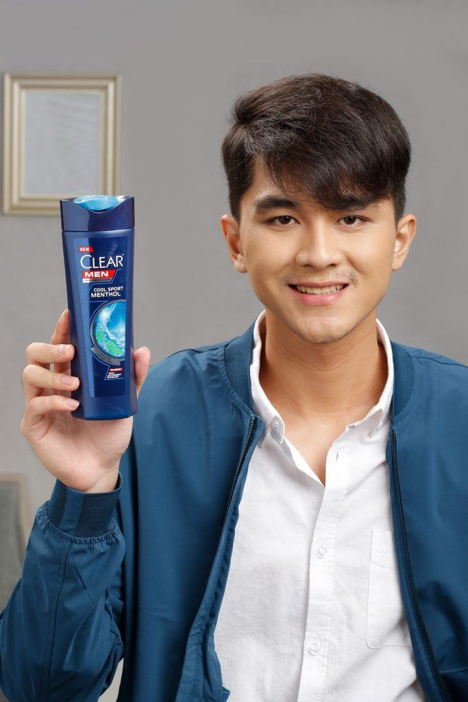 short hairstyles for men: guy holding a bottle of shampoo
