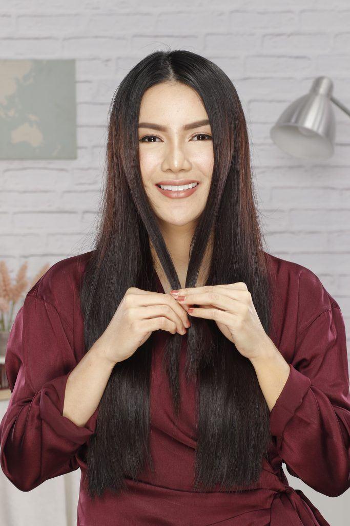 how to braid long hair: Girl is holding two sections of her hair for braiding