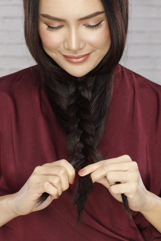 how to braid long hair: Girl is braiding her hair and has reached the tip