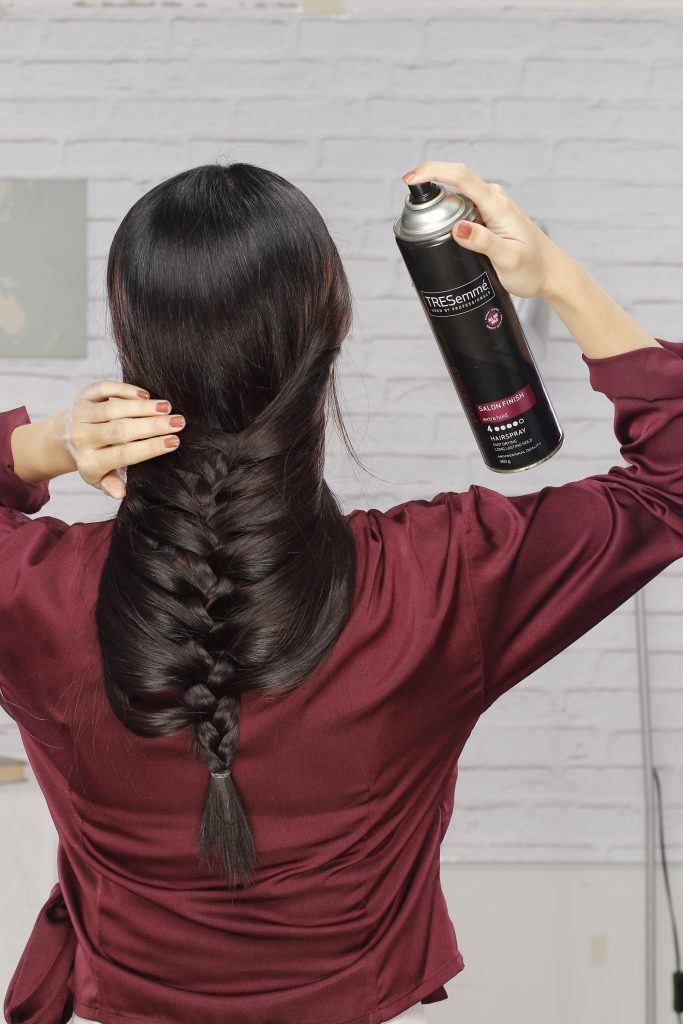 how to braid long hair: Girl is spritzing her hair with hairspray