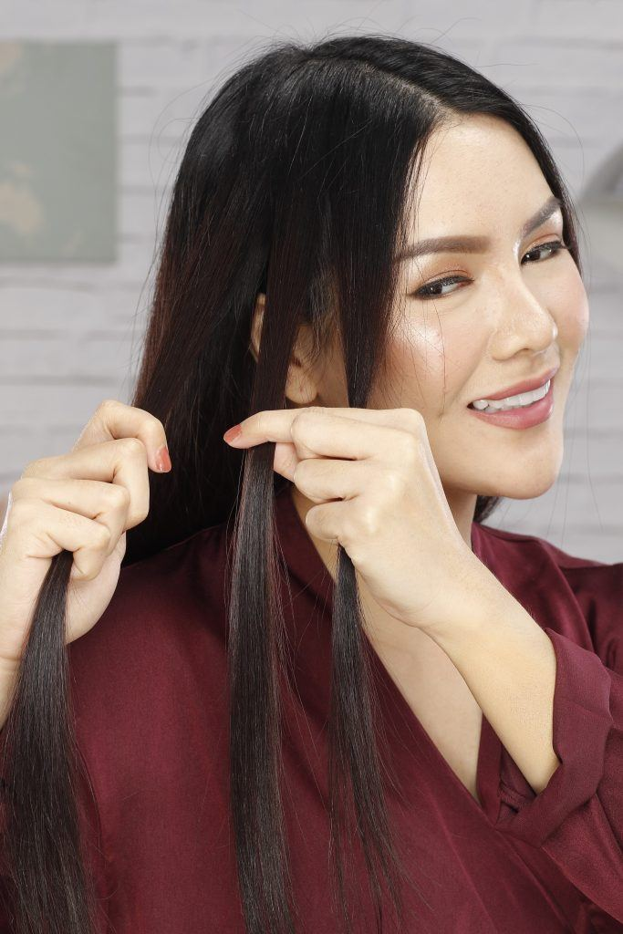 how to braid long hair: girl is showing how she makes a small braid on her hair