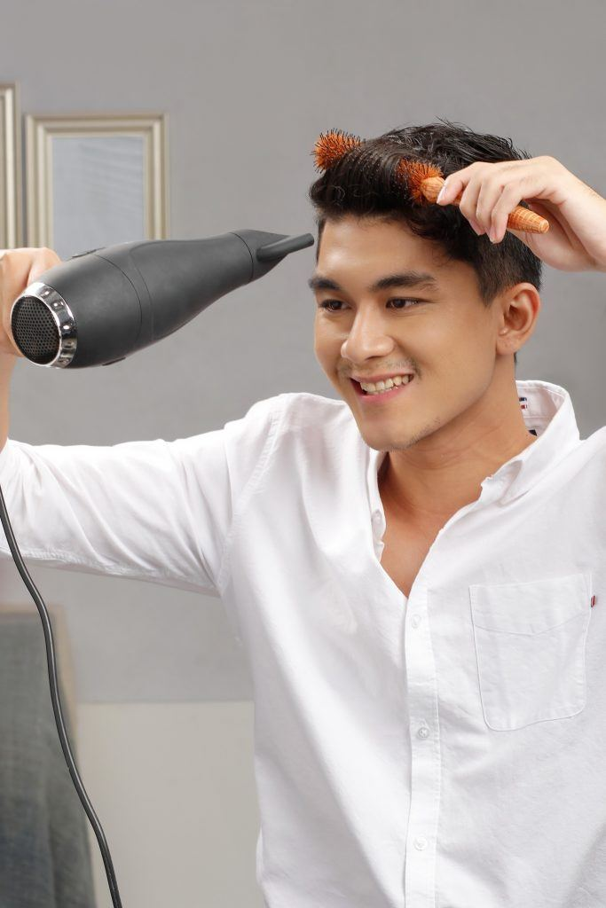 short hairstyles for men: guy is using a roller brush as he blow-dries his hair