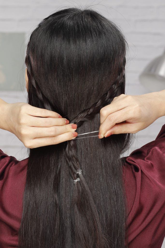Girl's back view is seen to show her tying the two braids together.