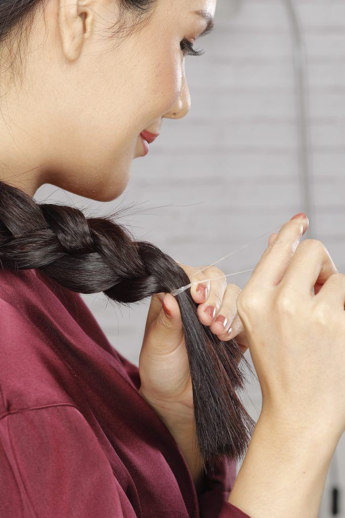 Girl is tying the tip of her braid