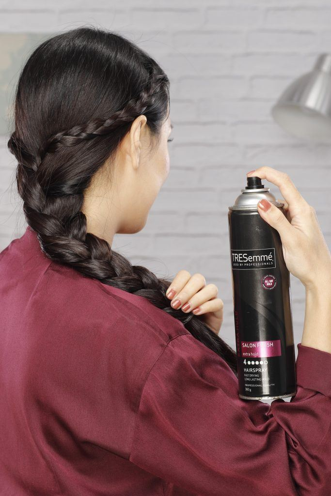 how to braid long hair: Girl's back view reveals her spraying her hair with hairspray
