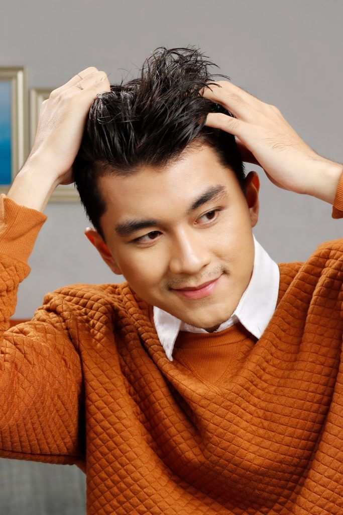 short hairstyles for men: guy is scrunching his hair